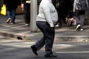 Pedestre com sobrepeso atravessa rua (Foto: David Gray/Reuters)
